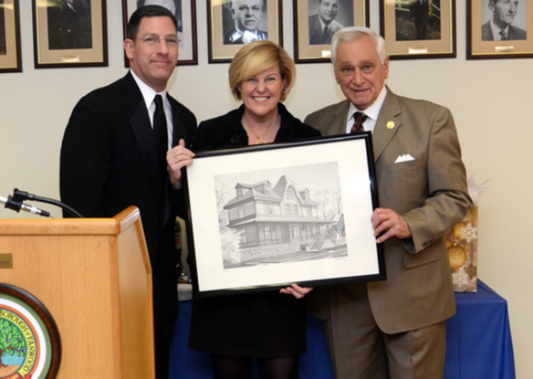 Former Councilman (now Borough Attorney) Russ Huegel and Mayor Colleen Mahr present a print of the historic Fanwood train station to Tony Parenti during his final meeting as a Councilman.
