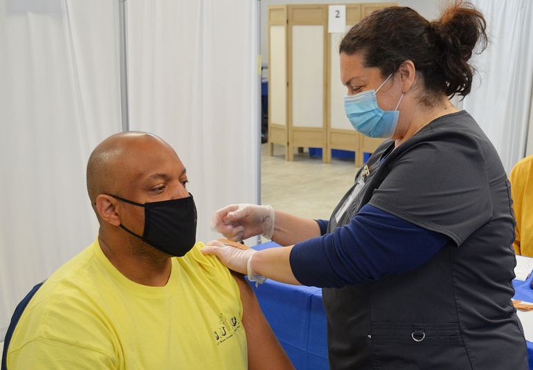 Pastor Shawn Wallace of St. John's Baptist Church receives COVID vaccine from Carolyn Sorge.