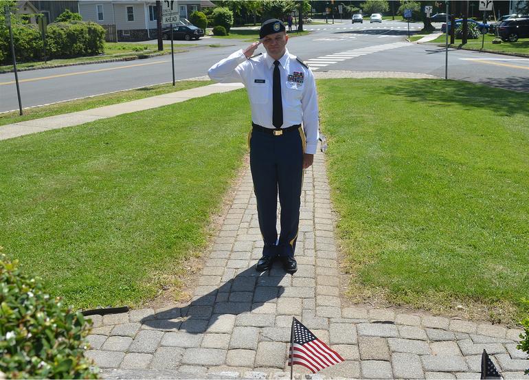 Patrick Moore salutes fallen veterans at Fanwood Memorial Library monument.