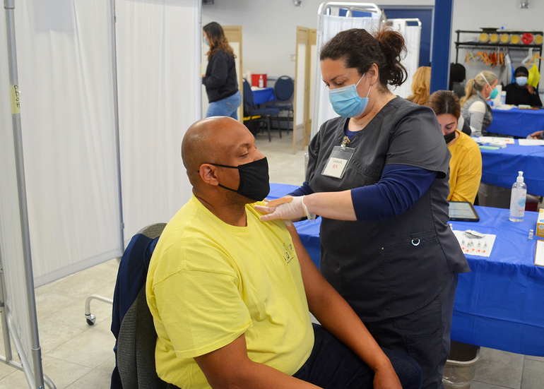 Pastor Shawn Wallace of St. John's Baptist Church in Scotch Plains receives COVID vaccine from Carolyn Sorge.