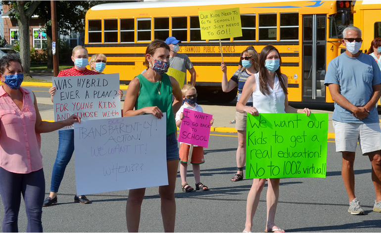 Parents with signs in support of in-class instruction at Scotch Plains-Fanwood schools.