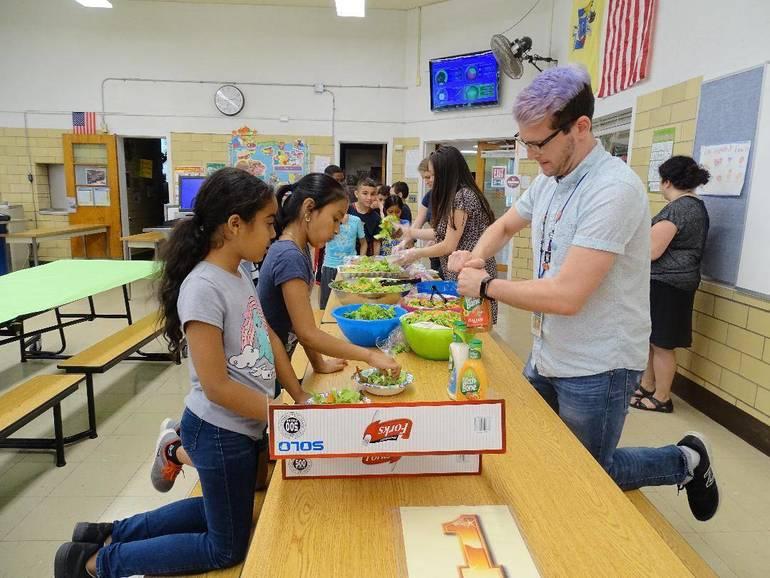 Jack Meyers, Grade 3 bilingual teacher at Pine Grove Manor Elementary School, helping students prepare their salads