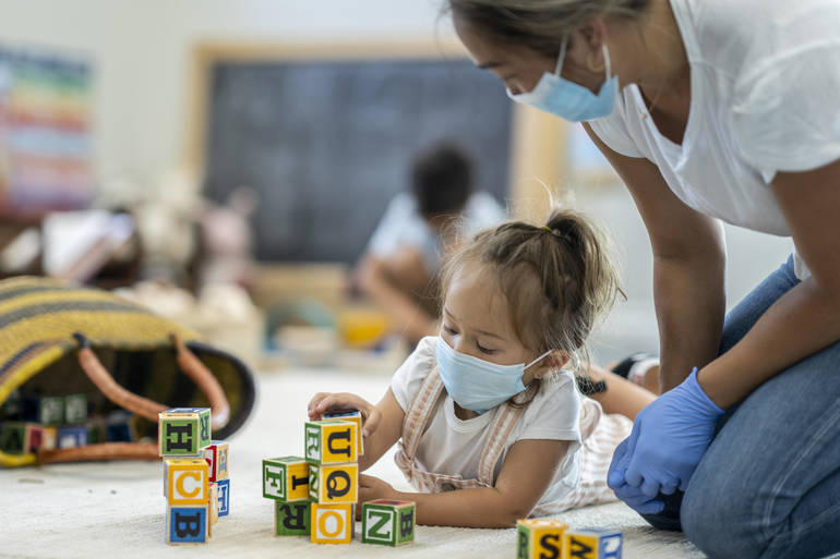 A young girl wearing a mask plays with blocks alongside a caregiver wearing PPE.
