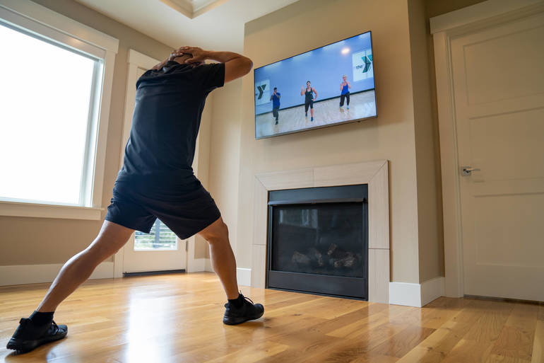 A YMCA member exercises in his living room while watching a fitness video.