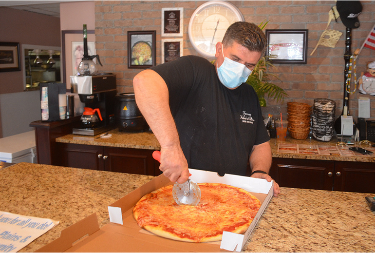 Ronnie Vojka of Fabio's Bistro in Fanwood cuts a pizza.png