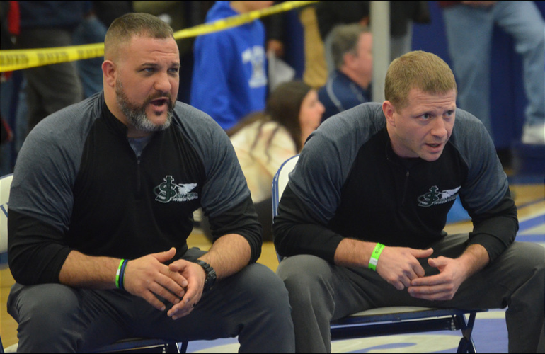 Saint Joseph wrestling coaches cheer on their athletes..png