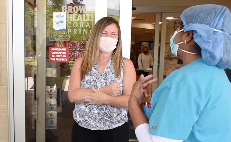 Lisette Caro speaking to a Broward Health Coral Springs staff member.