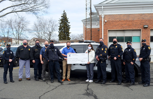 Members of the Scotch Plains police department present a check for $21,700 to Ellen Schisler of Autism New Jersey.