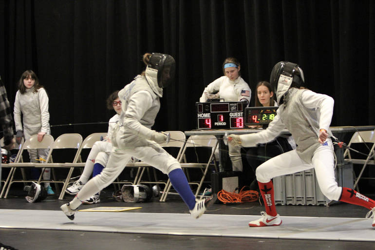 Senior foil Julia Shea (left, blue sock) is airborne on her way to winning a bout on Super Saturday.jpg