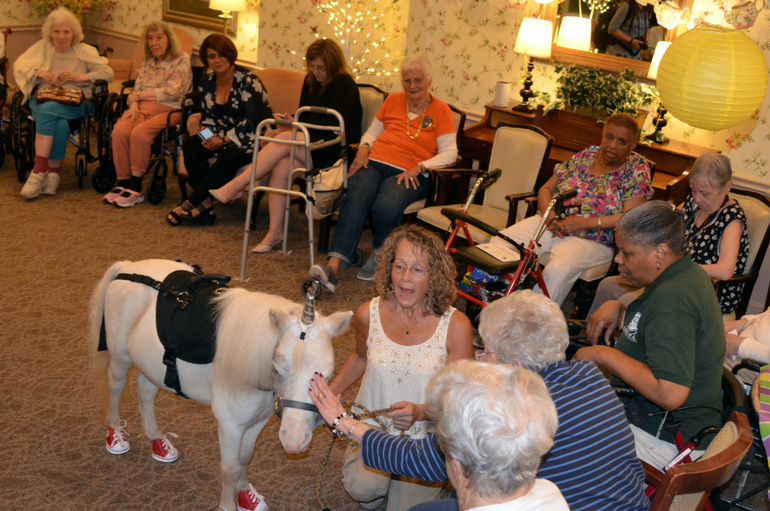 Seniors at The Chelsea at Fanwood interact with Noble The Unicorn