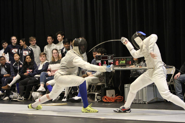 Senior foil Lucas Piccininni (left, blue sock) makes contact during a winning bout on Super Saturday.jpg