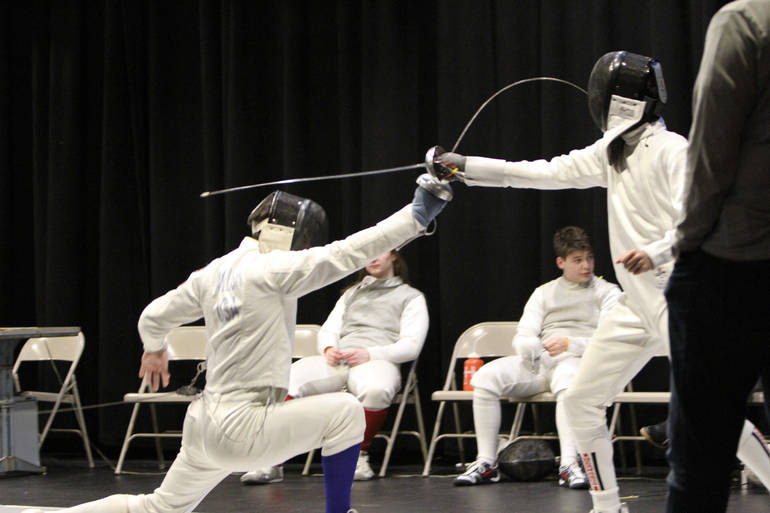 Senior epee John Walsh makes contact while lunging low to evade opponent on Super Saturday.jpg