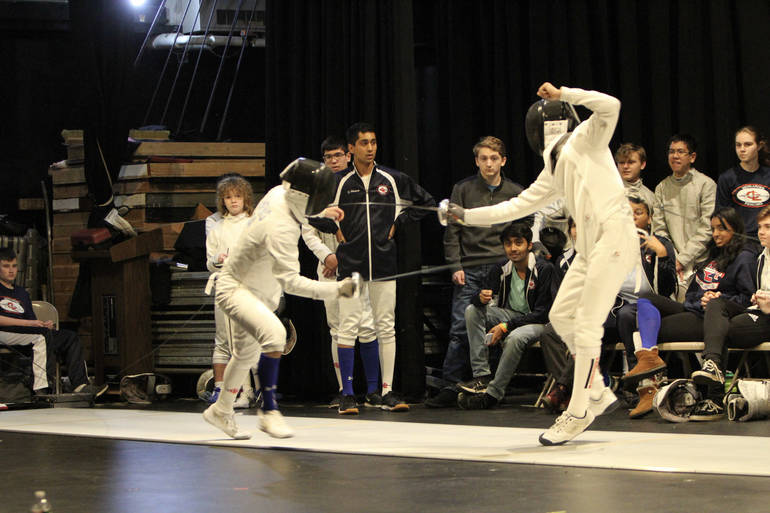 Senior epee Chris Zheng (left, blue sock) prepares a fleche to win the bout and tie the score at Super Saturday.jpg