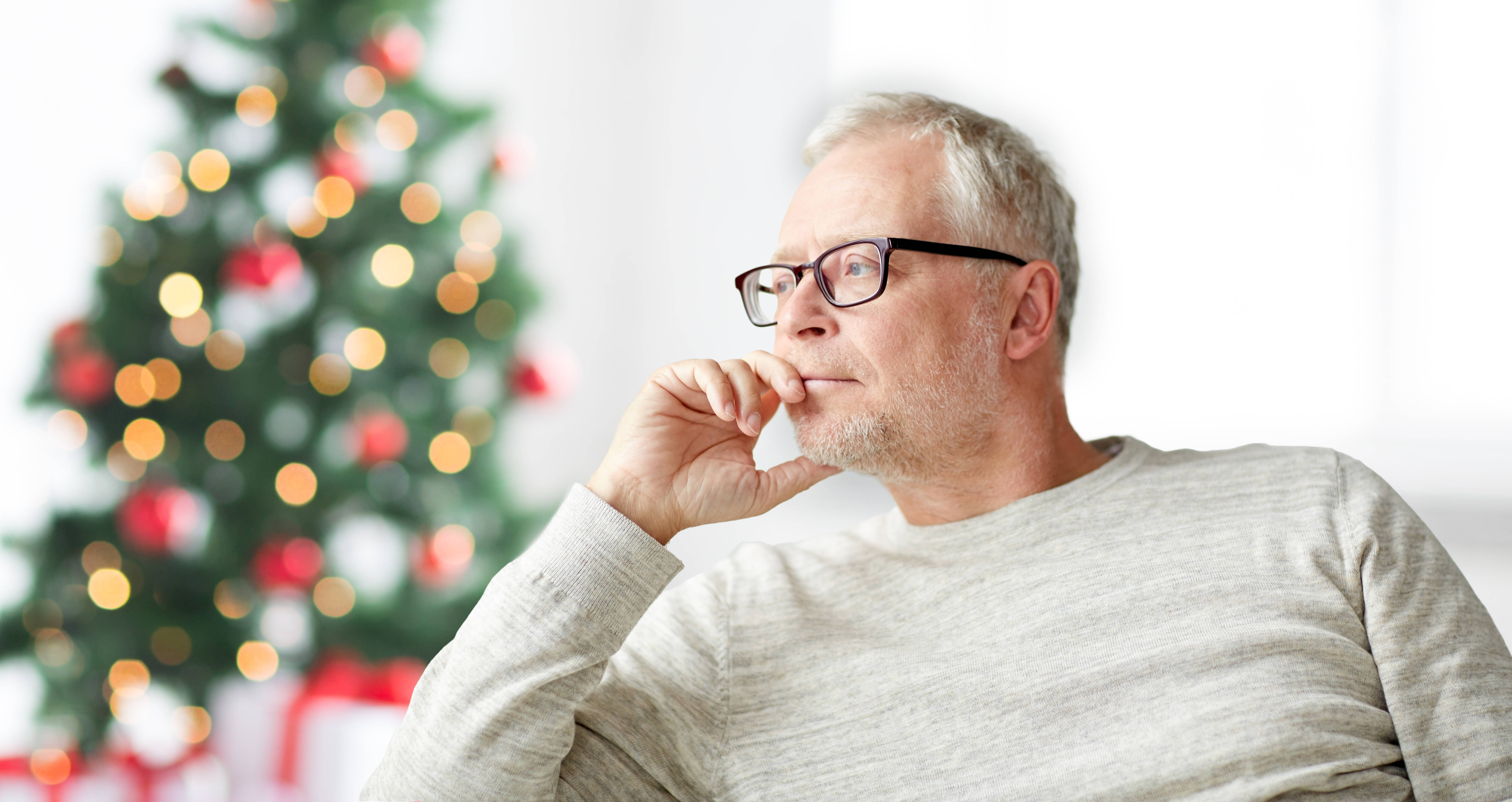 shutterstock_517386796 older man with christmas tree blurred in background.jpg