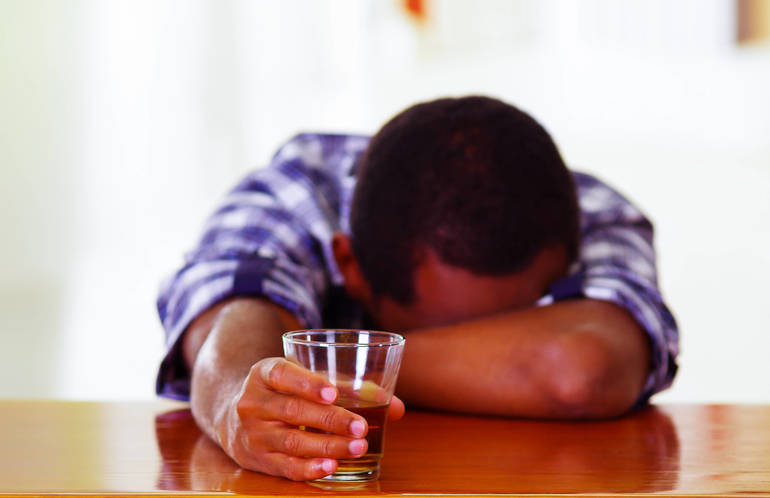 Lower Merion Police Drunk man asleep at bar drunk glass in hand wearing blue and white shirt.jpg