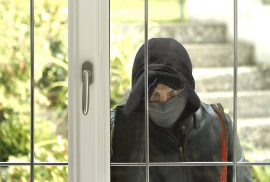 Top story 7dd20a531815f90a005c shutterstock 227615845 burglar peering into rear door about to break in