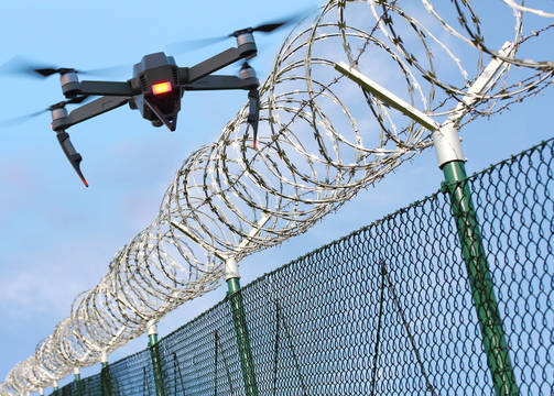 Top story c25fc61fdb013cb6ac2e shutterstock 790134829 prison fence with drone
