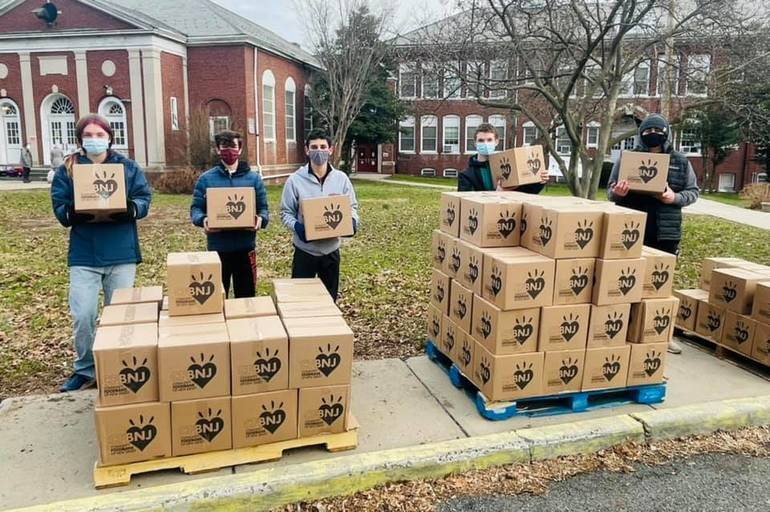 YMCA staff and volunteers hand out boxes of food.