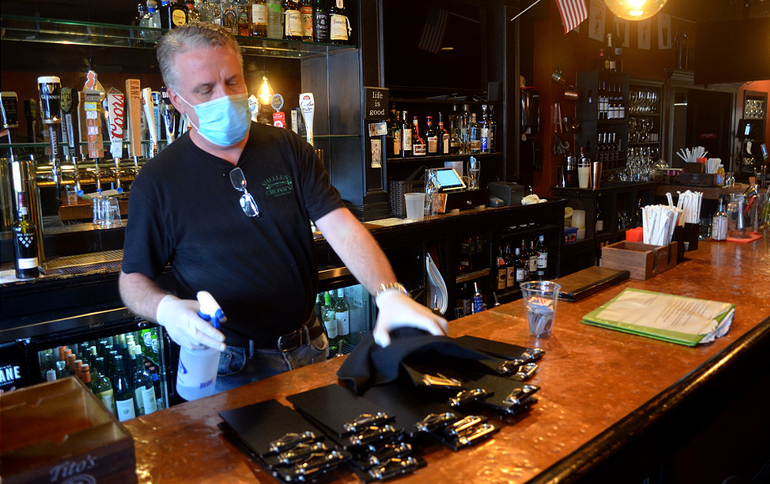 Tom McAuliffe sanitizes the bar and clipboards at Sheelen's Crossing in Fanwood.png
