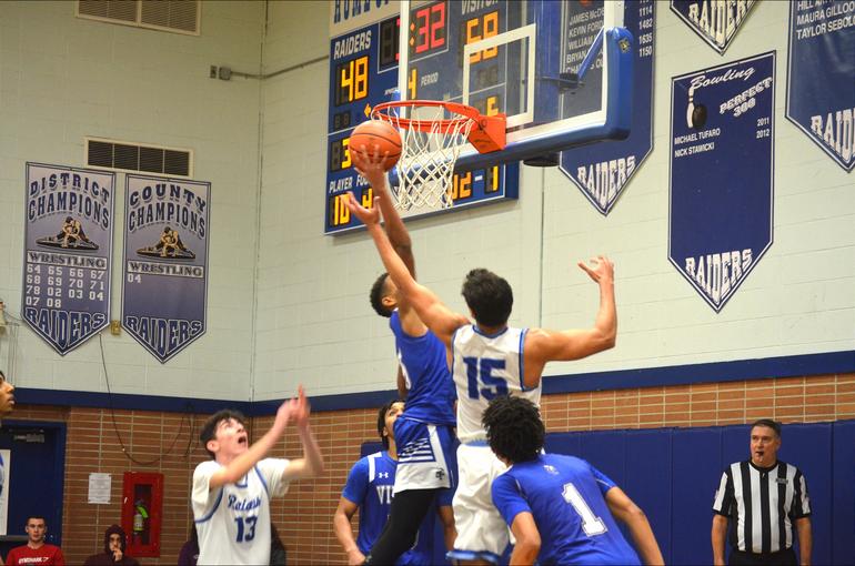 Union Catholic player drives to the basket as Scotch Plains-Fanwood's Justin Fletcher (15) defends.