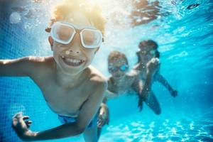 Children swimming underwater in a pool.