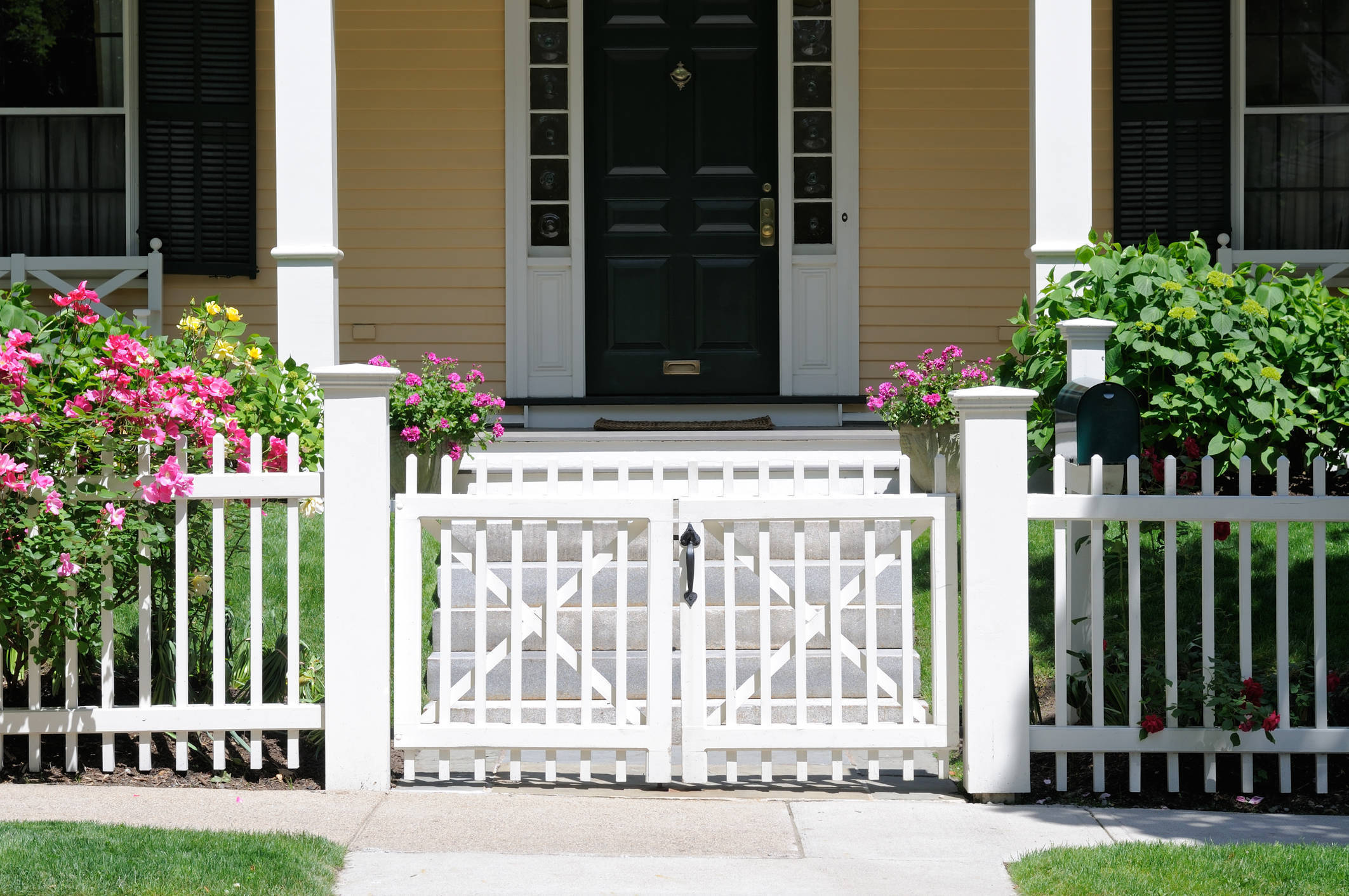 yellow house porch pink flowers april sparta living.jpg