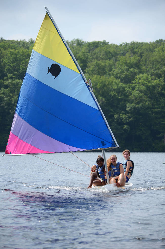A group of campers ride a sailboat.