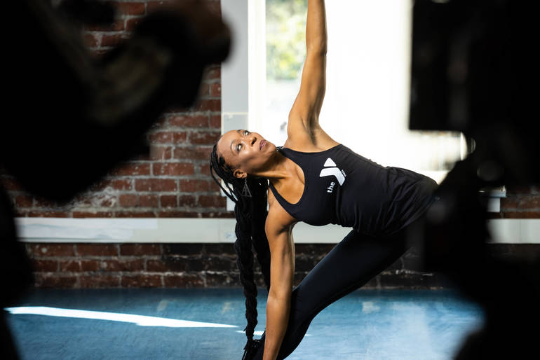 Fitness instructor demonstrates a stretch.