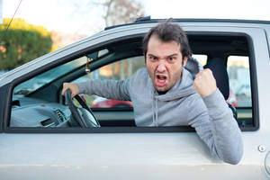 Angry driver pointing out the window of his car.