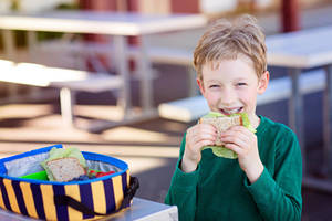 A young boy eating lunch at an outdoor table.
