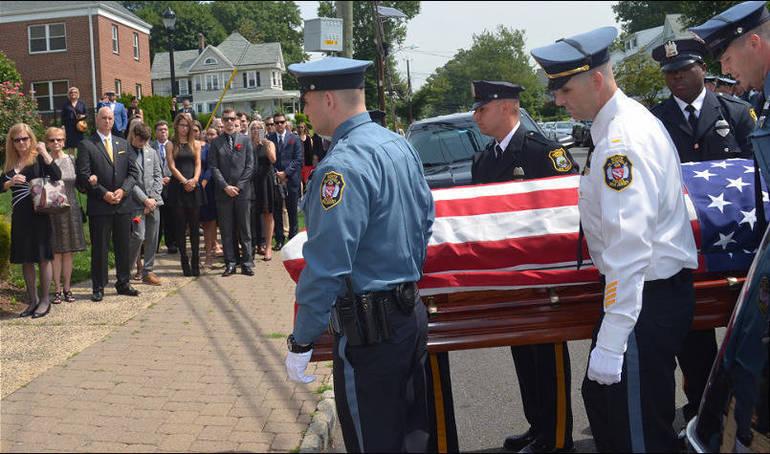 Chief Parenti casket enters church.png