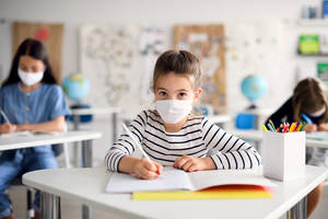 Child with face mask back at school after covid-19 quarantine and lockdown, writing.
