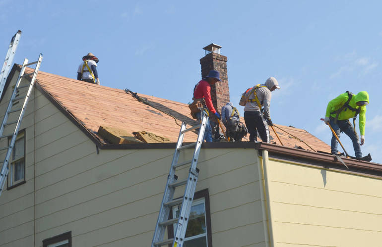 Workers from Deegan Roofing repair the damage to the roof of an elderly Scotch Plains man who was scammed by an individual he paid to fix his roof.