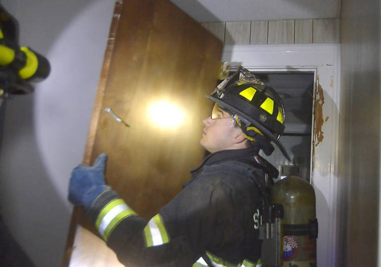 fire5 - Firefighter removes door inside vacated rectory.png