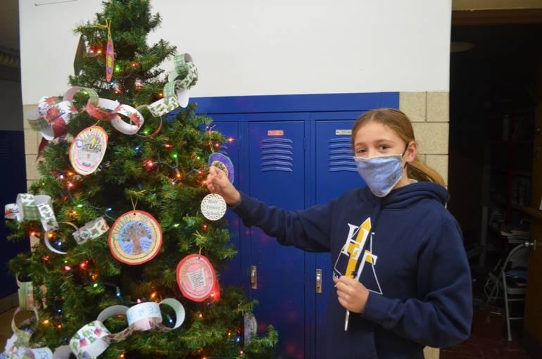 Sierra Warjanka, a 7th grader at Holy Trinity, puts an ornament on a Christmas tree.
