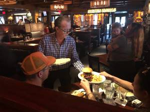 Greg Sherman, co-owner of Big Bear Brewing Company in Coral Springs, serves meals during staffing shortages.