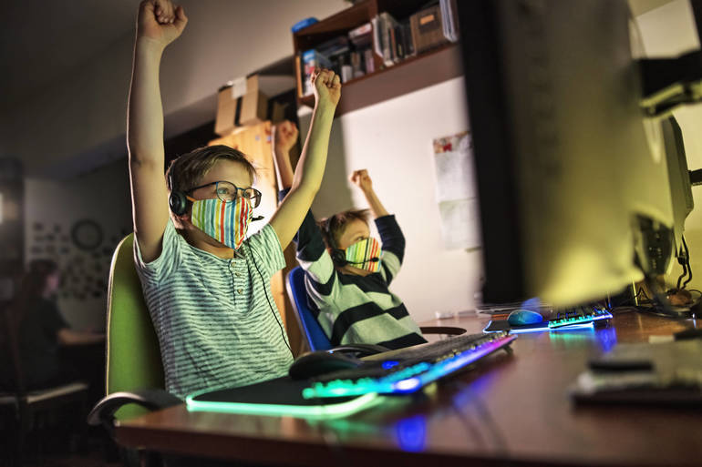 Two boys at computer throw their hands up in victory.