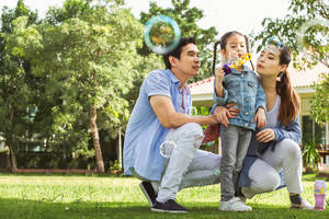 Asian family with young daughter outdoors, blowing bubbles.
