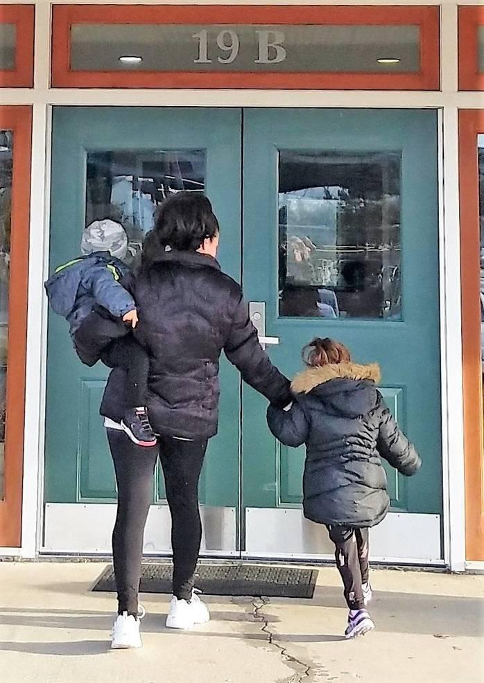 Mom plus 2 children enterig building.jpg