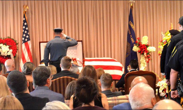 Parenti  - Officer salutes casket.png