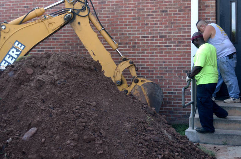 Plumber Glenn Natale and a Scotch Plains DPW watch as machine digs down to the sewer line.