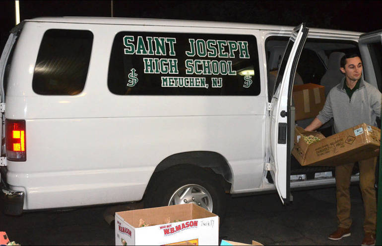 SJS - Saint Joseph High School teacher Charles Neto helps load a delivery van with sandwiches..png