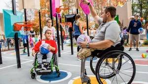 People in wheelchairs and people standing play a game on a color-coded basketball court